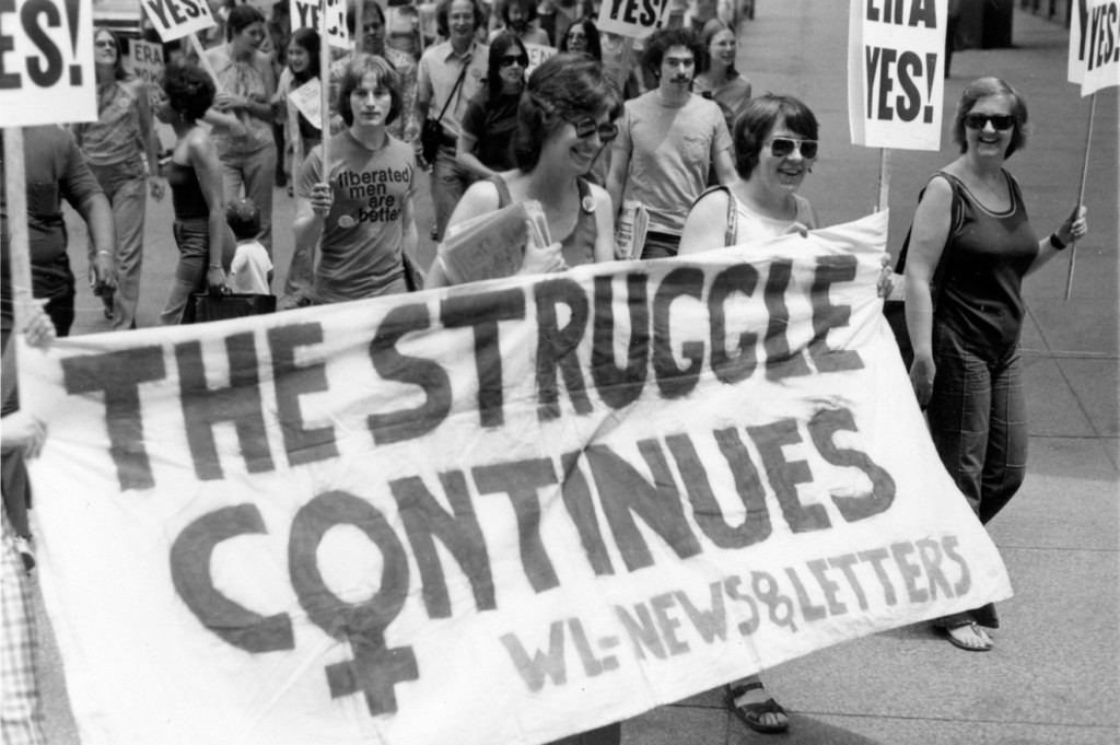 Suzanne French, Jane McKeever, and Mary Joan Schmidt holding banners and signs in an ERA march on 05/14/1977